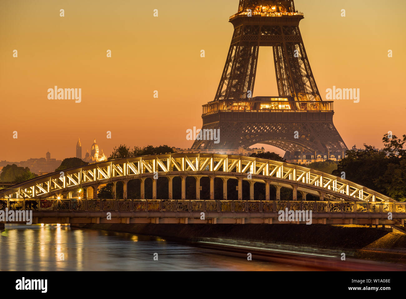 Paris, 75016, FRANCE: Eiffel Tower and Rouelle Bridge at Sunrise with the Basilica of the Sacre Coeur in the distance. Ile-aux-Cygne Stock Photo