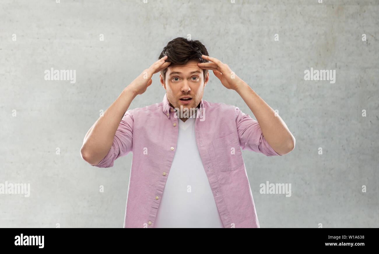 man touching his head over grey concrete wall - Stock Image