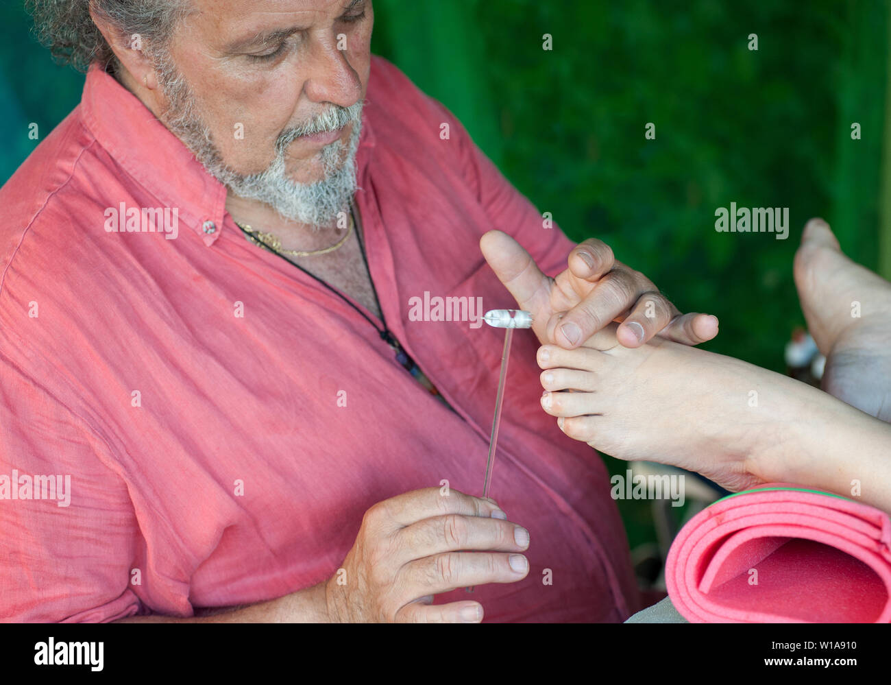 Professional masseur during a session of plantar reflexology, tapping with a tiny hammer - Stock Image