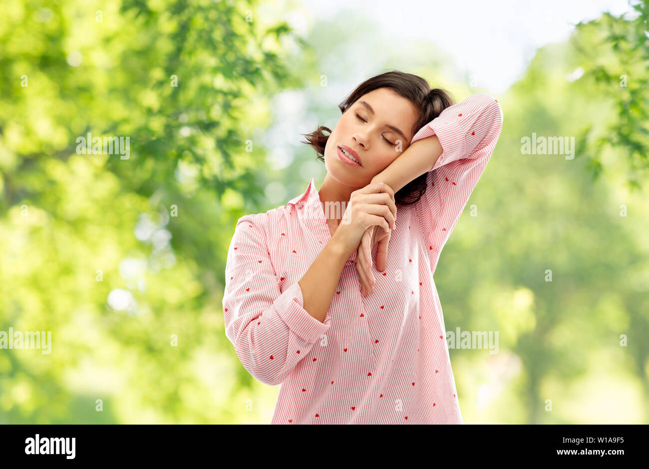 woman in pajama napping over natural background - Stock Image