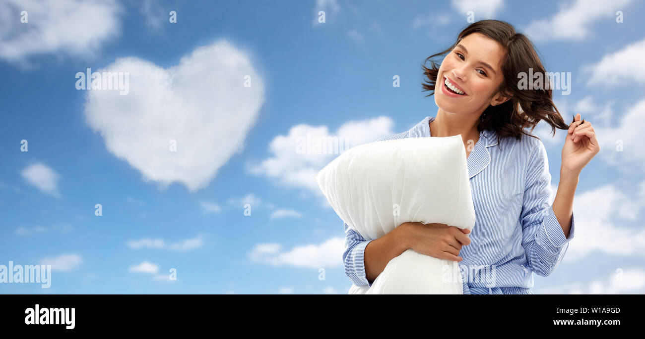 happy young woman in pajama with pillow over sky - Stock Image