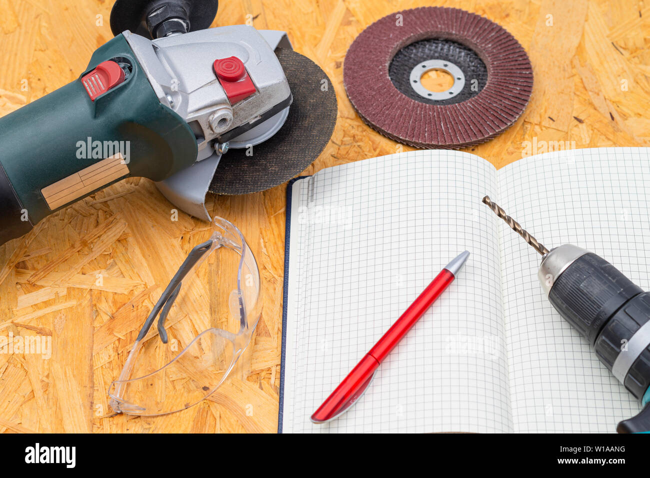 The image shows an angle grinder with a driller and notebook on a wooden table - Stock Image