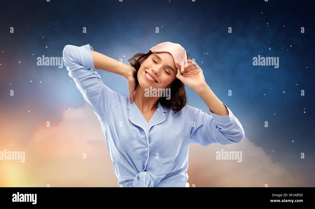 happy young woman in pajama and eye sleeping mask - Stock Image