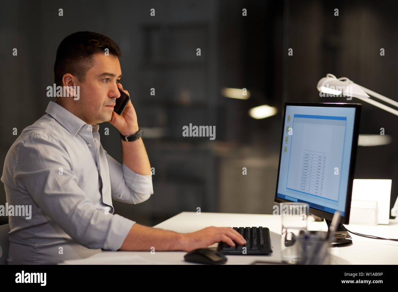 businessman calling on sartphone at night office Stock Photo