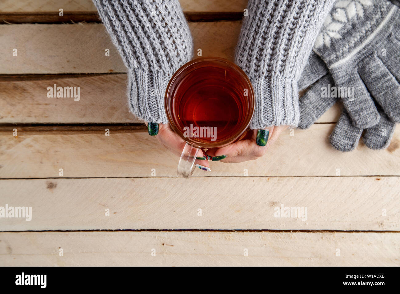 women's hands holding a vintage mug on a wooden background Stock Photo