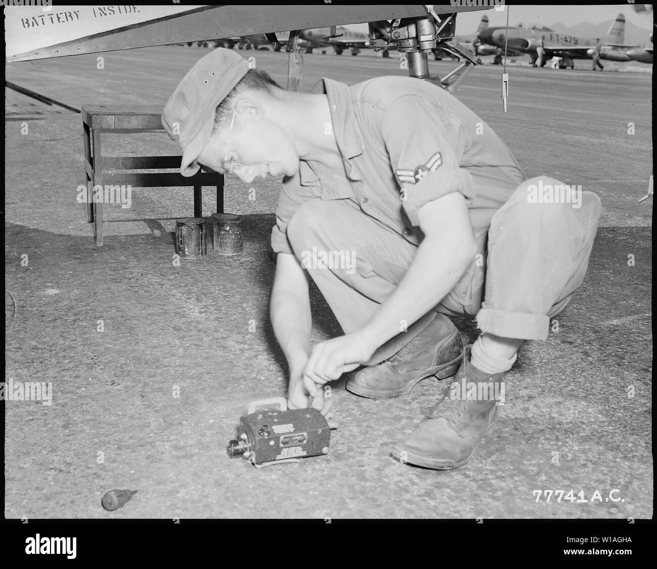 AERIAL BROWNIE. Gun cameras are synchronized with the .50 calibre machine gun fire on U.S. Air Force F-80 jet fighters and record every strike against the North Korean aggressors. Here, Cpl. Harvey Davis, 19, of Redfield, Kansas, inspects one of the gun cameras after an F-80 close support mission. - Stock Image