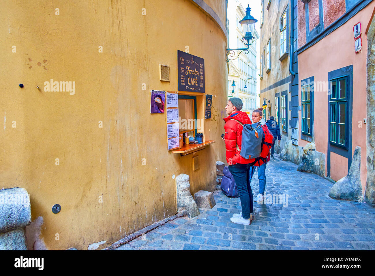 VIENNA, AUSTRIA - FEBRUARY 18, 2019: The tourists buy traditional coffee in small stylish Fenster cafe - tiny kiosk in historic house wall, hidden in - Stock Image