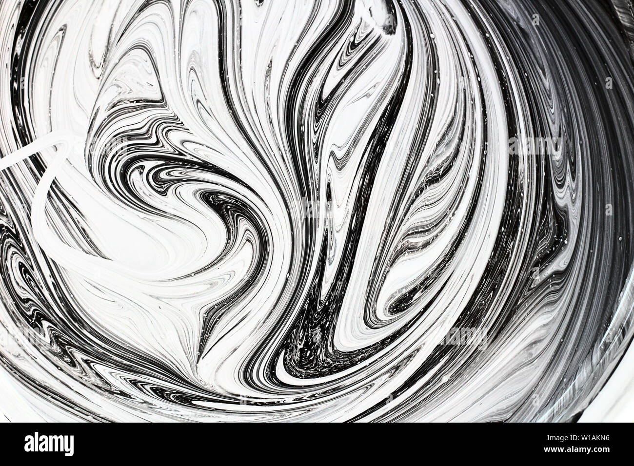 abstract image mixing of two colors. The texture of the circles of white and black paint Stock Photo