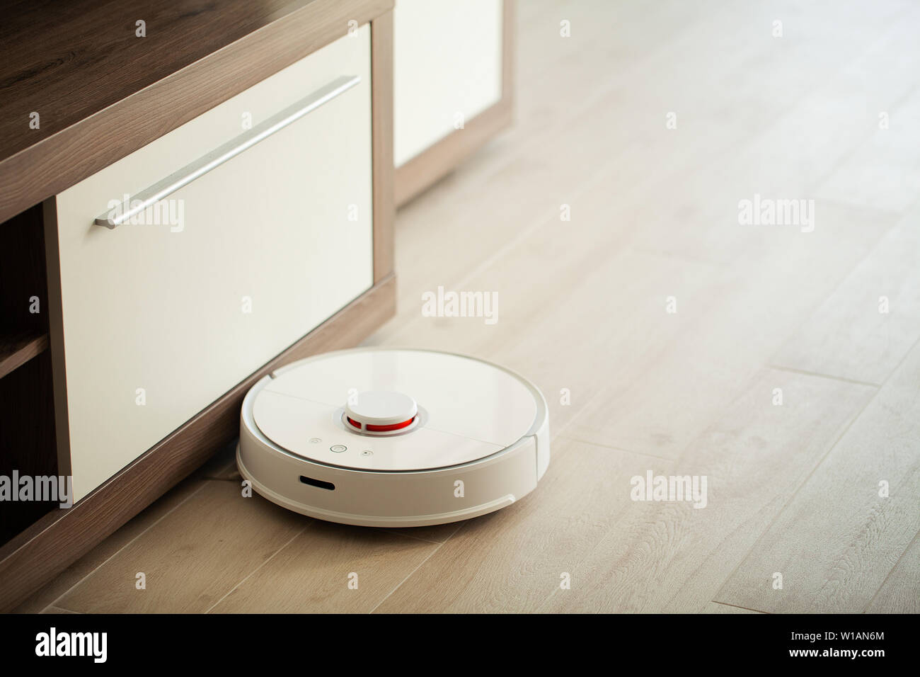 Smart House. Vacuum cleaner robot runs on wood floor in a living room. - Stock Image