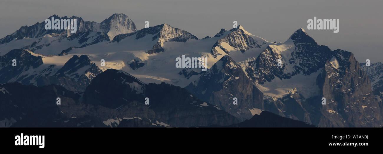 High mountains Finsteraarhorn, Schreckhorn and Ewigschneehorn just before sunset. Gauli Glacier, Switzerland. - Stock Image