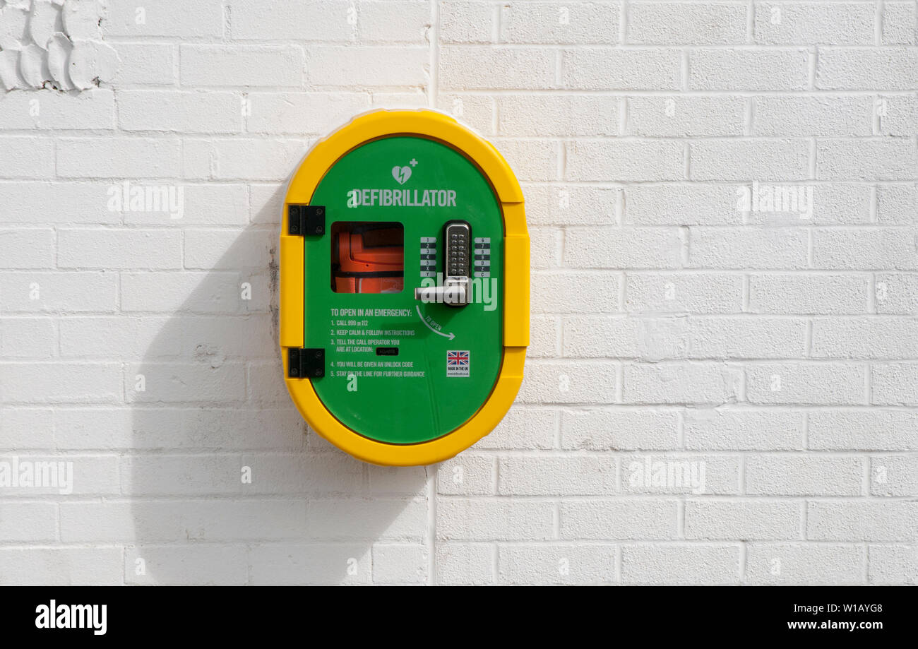 Defibrillator positioned on wall of building in sports area of local park Blackpool lancashire England UK - Stock Image