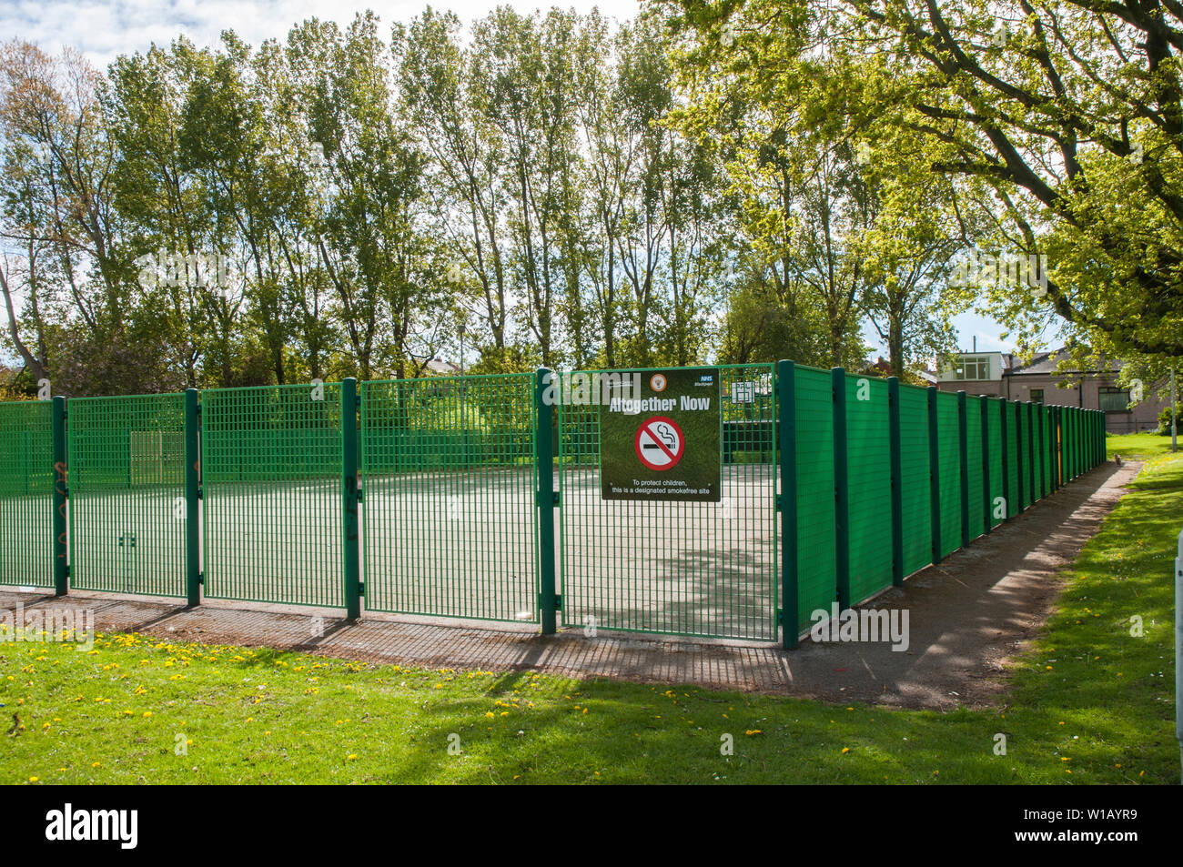 No smoking sign on fencing around sports area to protect children on local partk in Blackpool Lancashire England UK Stock Photo