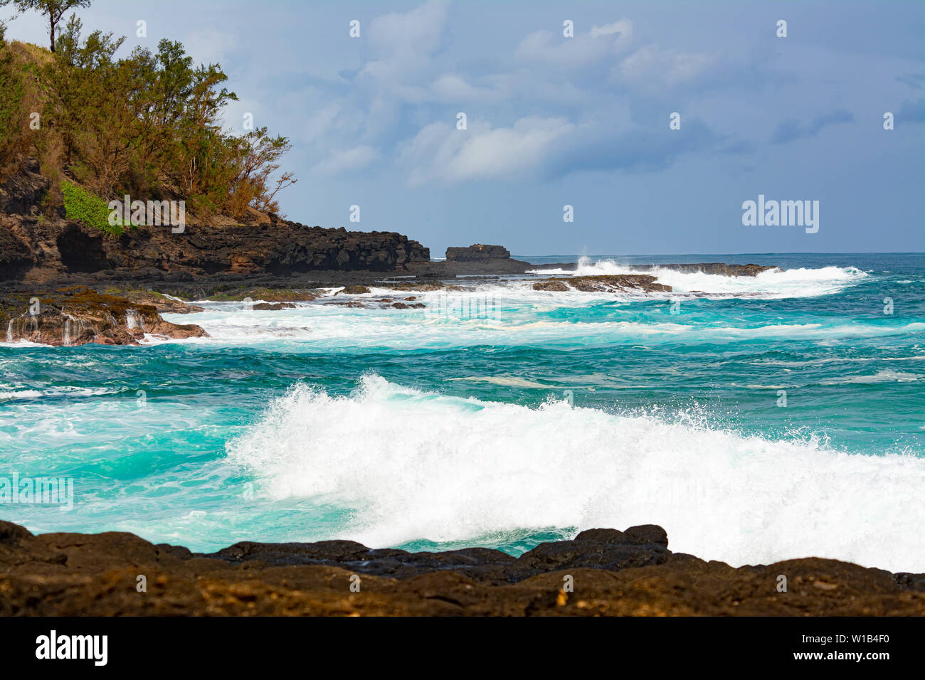 View of waves crashing into the lava rocks to the west of Secret Beach on the Hawaiian Island of Kauai Stock Photo
