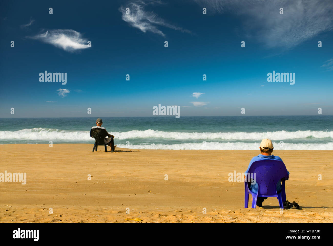 Two man looking onto the sea sitting on a sand beach on plastic chairs. Read view - Stock Image