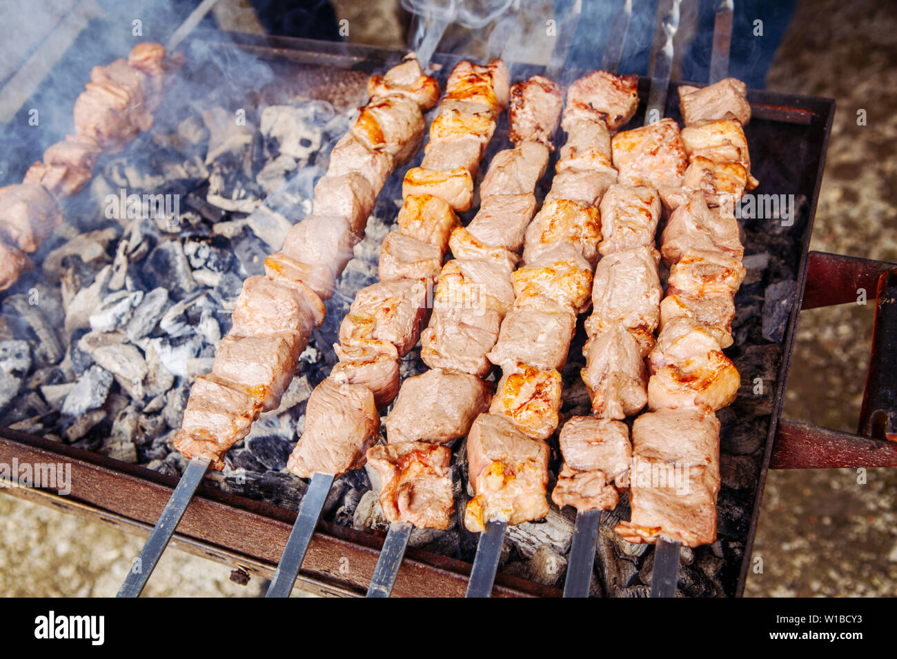 Closeup macro of raw roasted marinated meat barbecue shish kebab shashlik on steel metal skewers lying grill fire brazier with charcoal. Stock Photo