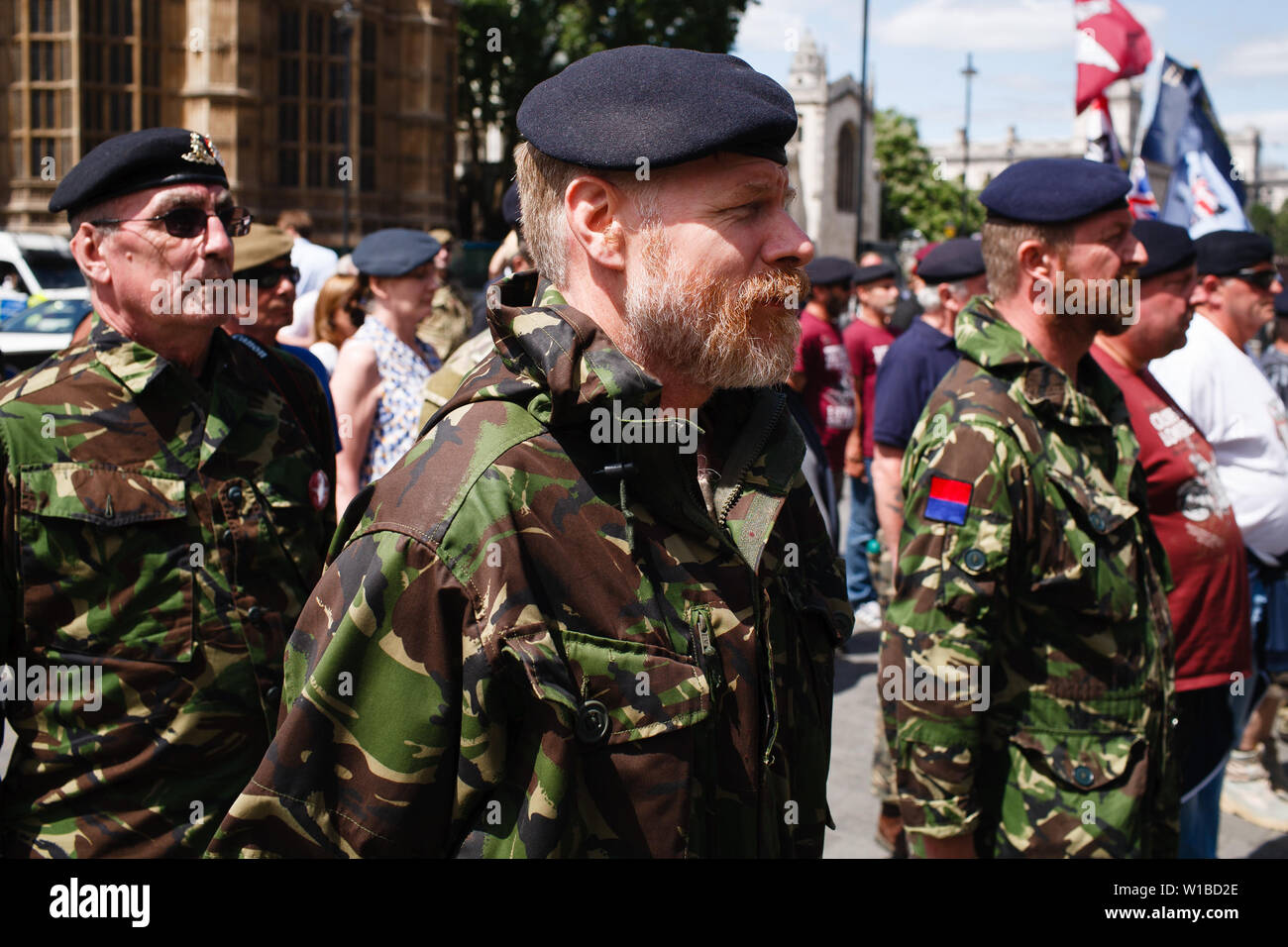 Veterans protesting the prosecution of former British soldiers for wartime killings stand in formation at a demonstration outside the Houses of Parliament. The demonstration centred on the ongoing case of the as-yet-unnamed 'Soldier F', charged with two counts of murder for killings on Bloody Sunday in Londonderry, Northern Ireland, in 1972. - Stock Image