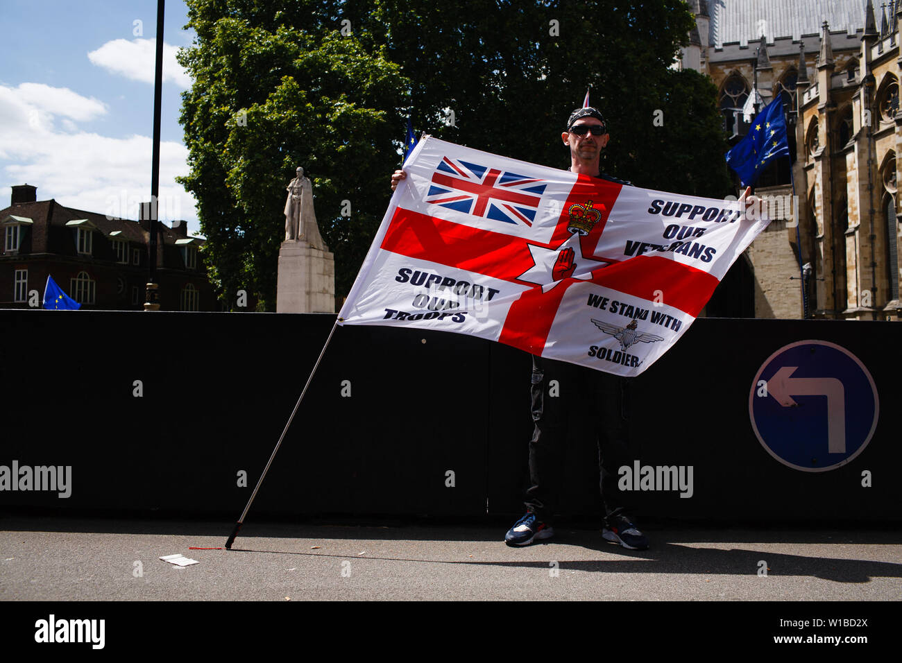 A veteran holds an English flag during a protest against the prosecution of former British soldiers for wartime killings held outside the Houses of Parliament. The demonstration centred on the ongoing case of the as-yet-unnamed 'Soldier F', charged with two counts of murder for killings on Bloody Sunday in Londonderry, Northern Ireland, in 1972. - Stock Image