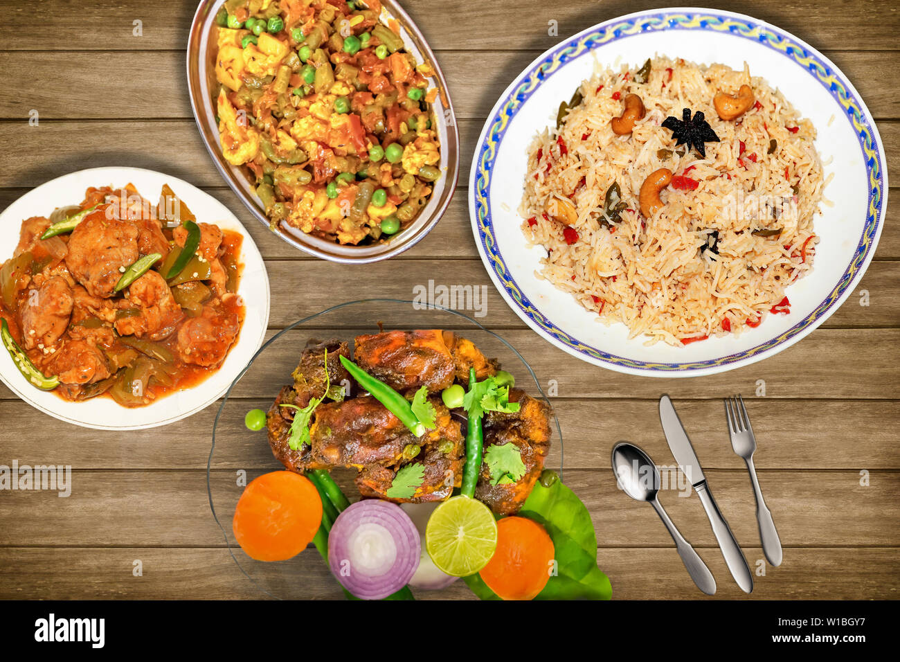 Tasty Indian food meal of fried rice with mixed vegetables along with red hot spicy lobster dish garnished with salad and spicy chili chicken Stock Photo