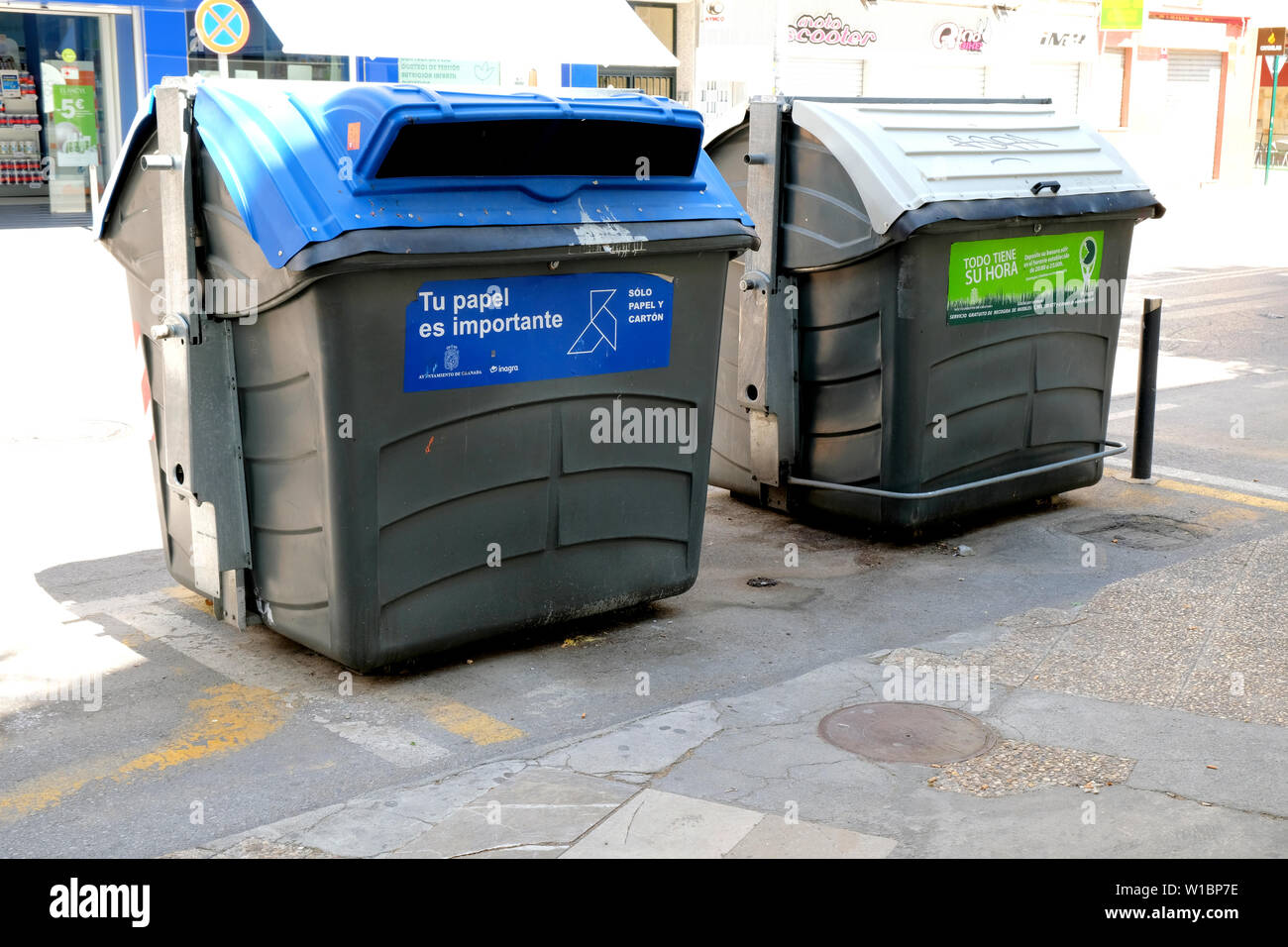 Trash and recycling bins side by side on a street in Granada, Spain; 'tu papel es importante' (your rolepaper is important). - Stock Image