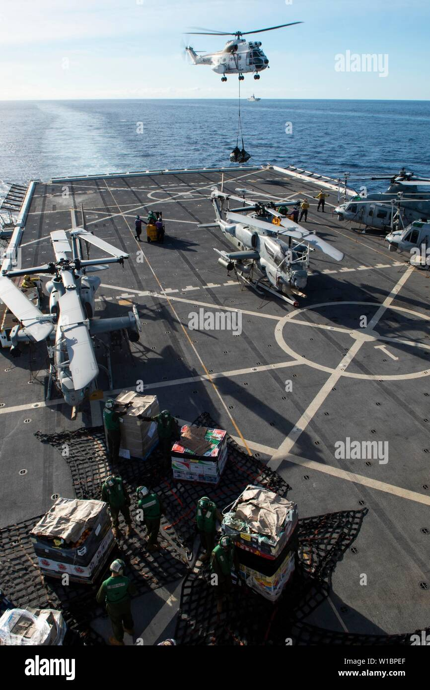 190616-N-DX072-1182 CORAL SEA (June 16, 2019) Sailors aboard the amphibious transport dock ship USS Green Bay (LPD 20) unloads pallets as an SA-330J Puma helicopter, assigned to the dry cargo and ammunition ship USNS Richard E. Byrd (T-AKE 4), transports cargo onto the flight deck during a replenishment-at-sea. Green Bay, part of the Wasp Amphibious Ready Group, with embarked 31st MEU, is operating in the Indo-Pacific region to enhance interoperability with partners and serve as a ready-response force for any type of contingency. (U.S. Navy photo by Mass Communication Specialist 2nd Class Anai - Stock Image