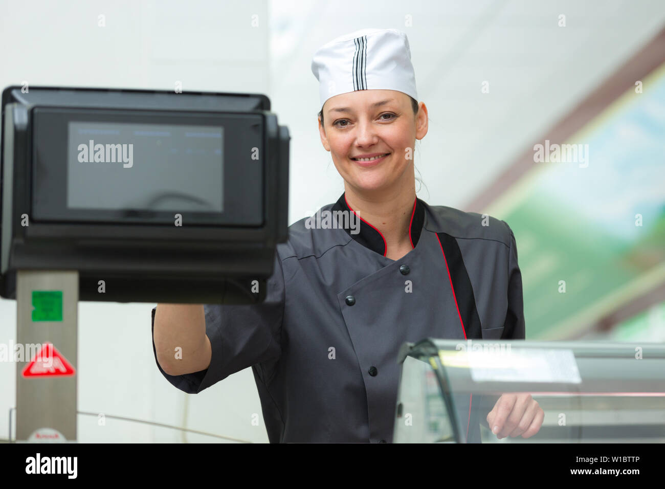 portrait of a smiling female shop keeper - Stock Image