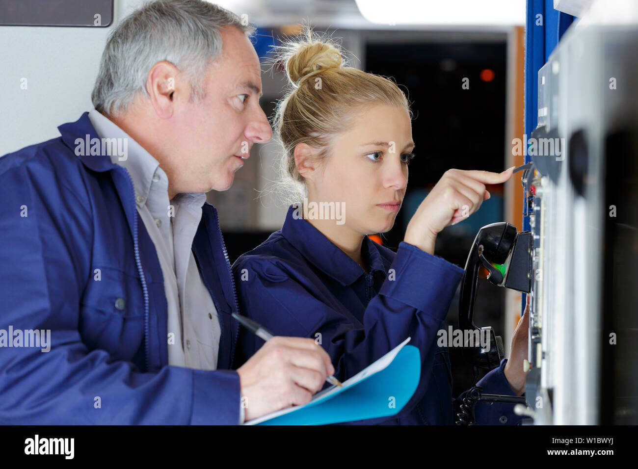 man and woman mechanics work with the appliance - Stock Image