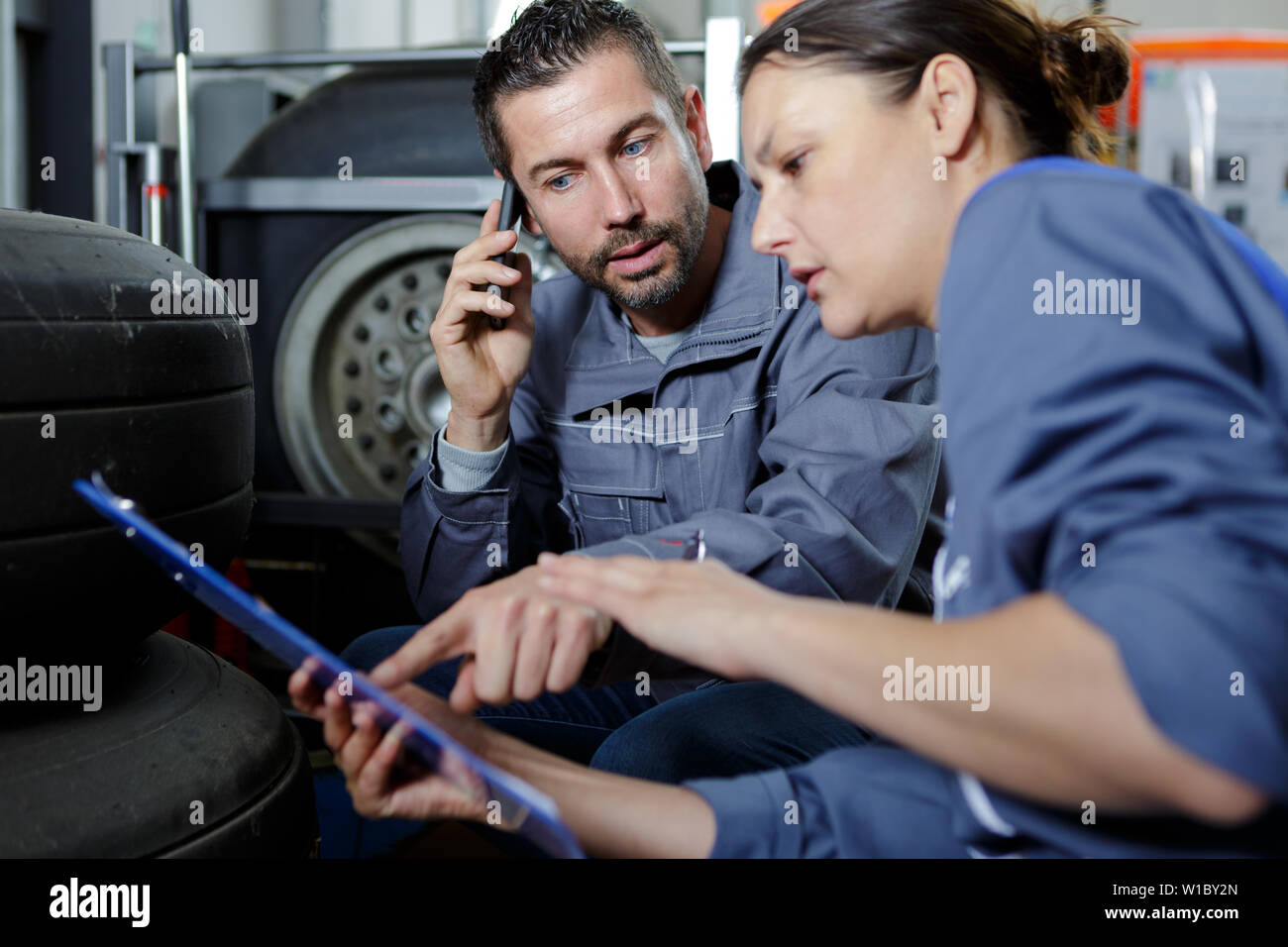 garage co-workers looking at clipboard and talking on smartphone - Stock Image