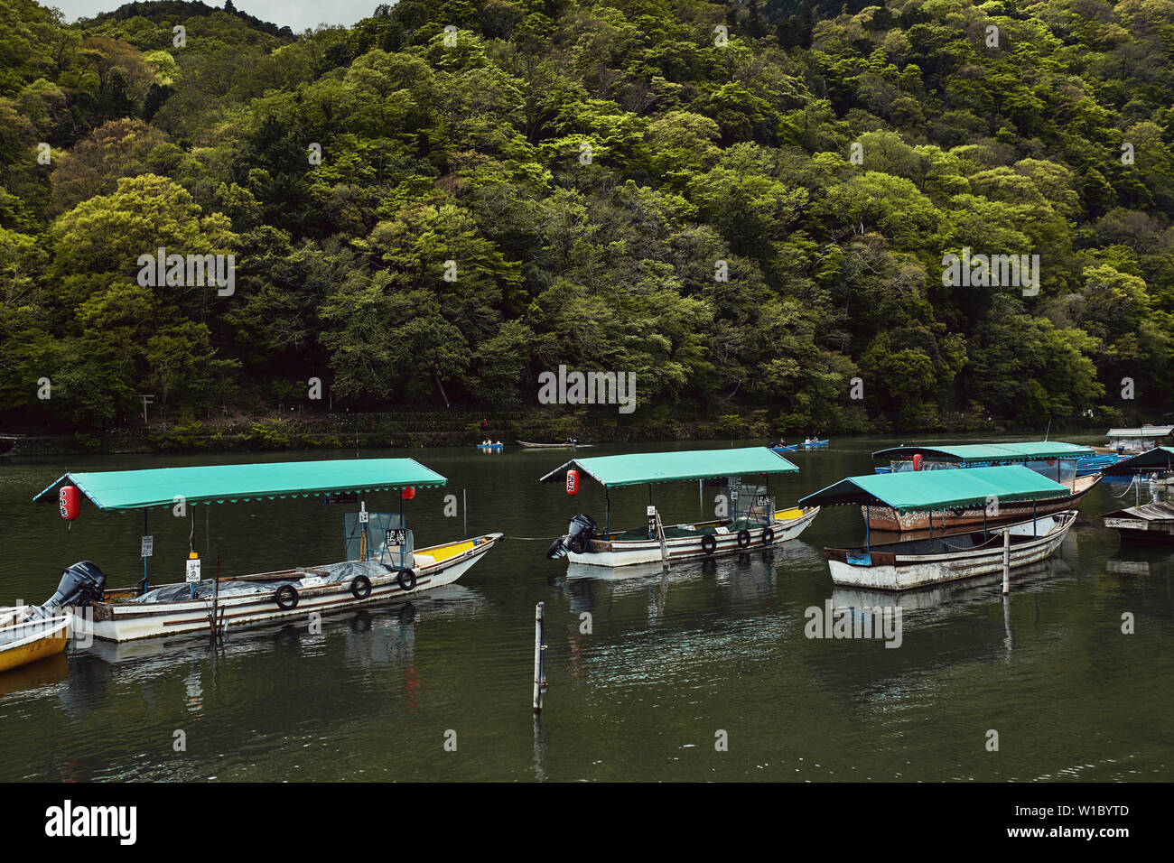 Boats lined up along the Hozu River in Arashiyama, Japan - Stock Image