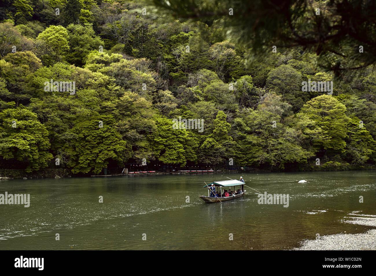 Tourists cruising down the Hozu River in Arashiyama, Japan - Stock Image