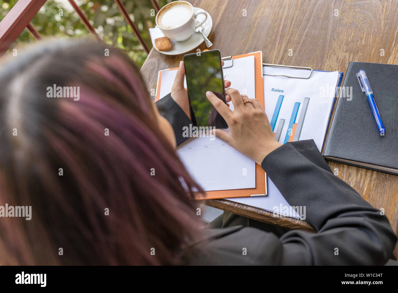 High angle view of woman hand tapping on cellphone screen - Stock Image