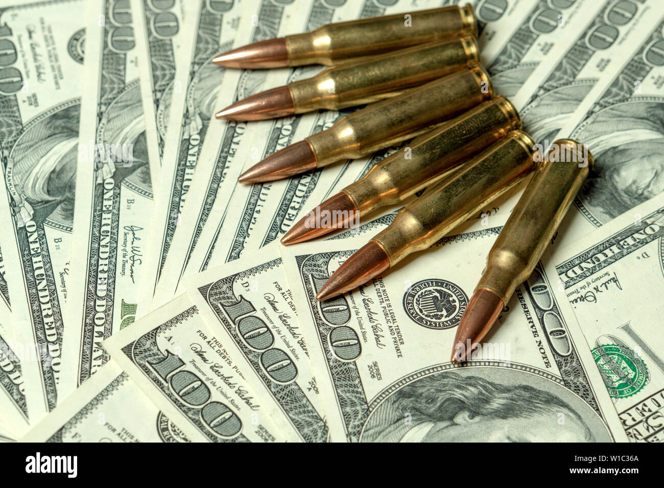 Rifle cartridges on dollars. Concept for crime, contract killing, paid assassin, terrorism, war, global arms trade, weapons sale. Illegal hunting - Stock Image