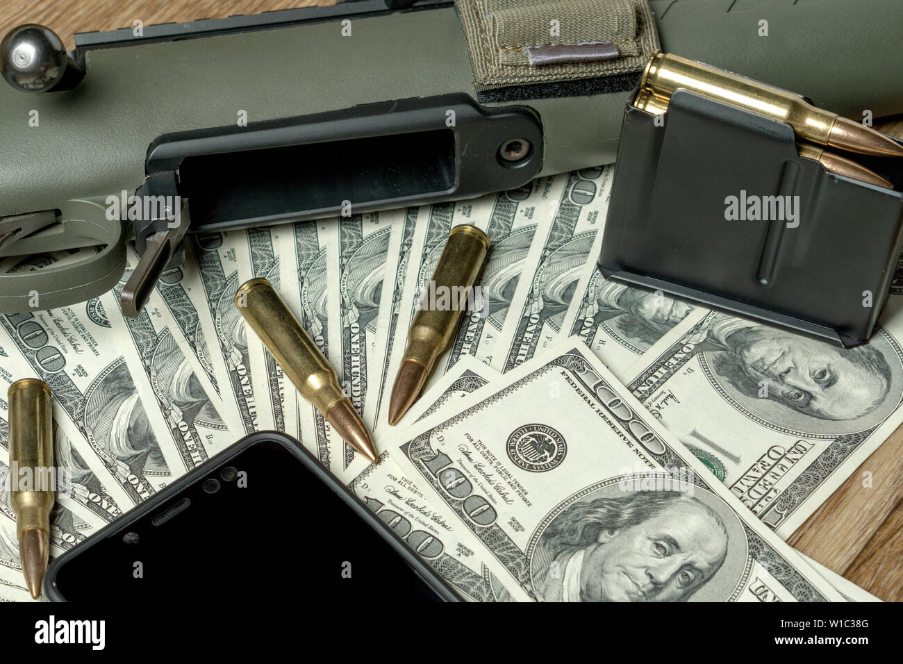 Rifle, magazine and cartridges on money. Concept for crime, contract killing, paid assassin, terrorism, war, global arms trade, weapons sale. Illegal - Stock Image