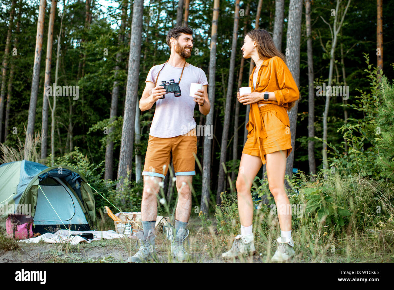 Young couple standing with hot drinks at the camping in the forest, enjoying their summer trip during the sunset Stock Photo