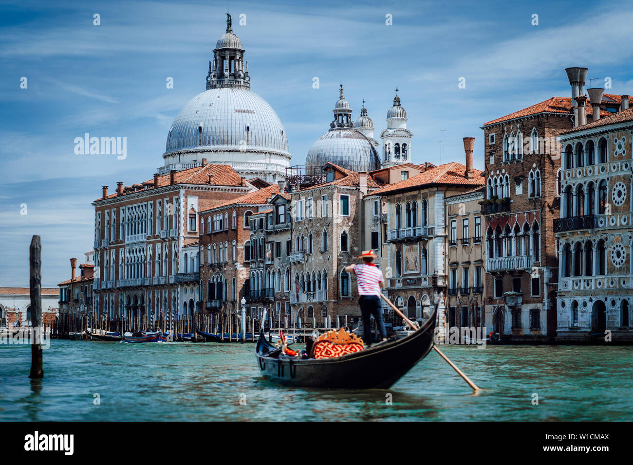 Traditional Gondola and gondolier on Canal Grande with Basilica di Santa Maria della Salute in the background in Venice, Italy. Summer vacation city Stock Photo