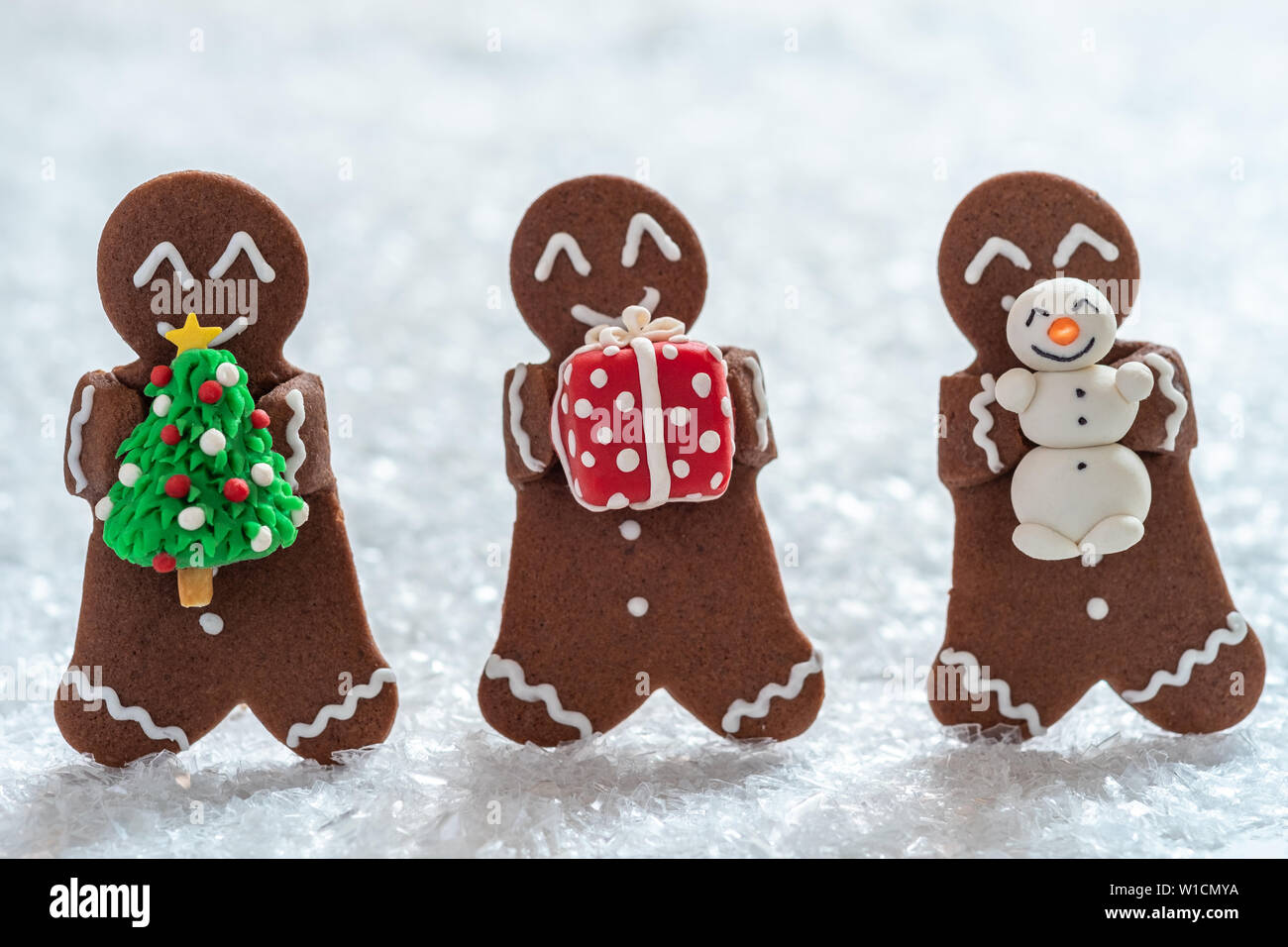 Funny Gingerbread cookie men with tiny marzipan snowman Stock Photo