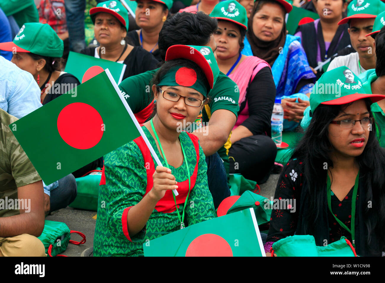 """Women participate in the event titled """"Lakho Konthe Shonar Bangla"""". Over 2.5 lakh people chorus national anthem at National Parade Square in a bid to Stock Photo"""
