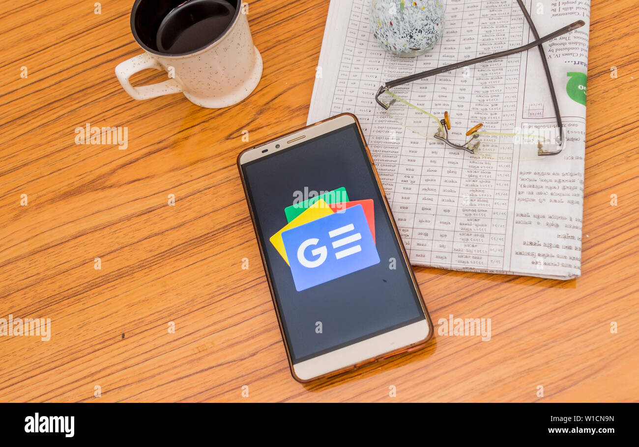 Kolkata, India, February 3, 2019: Google news app (application) visible on mobile phone screen beautifully placed over a wooden table with a newspaper Stock Photo