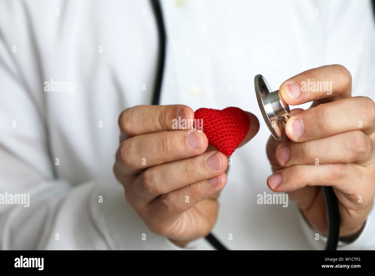Doctor with stethoscope and red knitted heart in hand. Concept of cardiologist, heart diseases, diagnosis, blood pressure, medical exam - Stock Photo