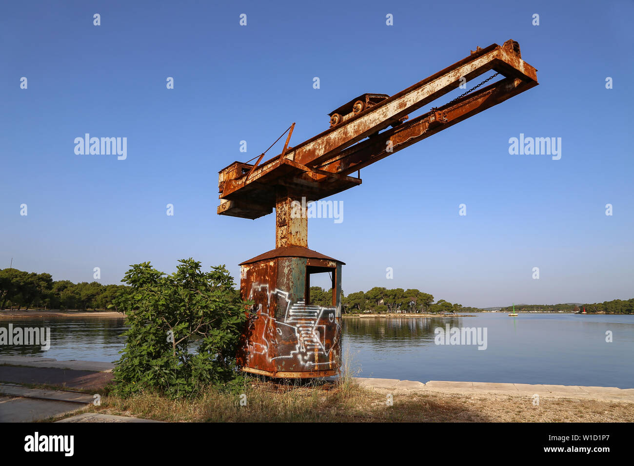 Old port crane rusts in the sun. - Stock Image