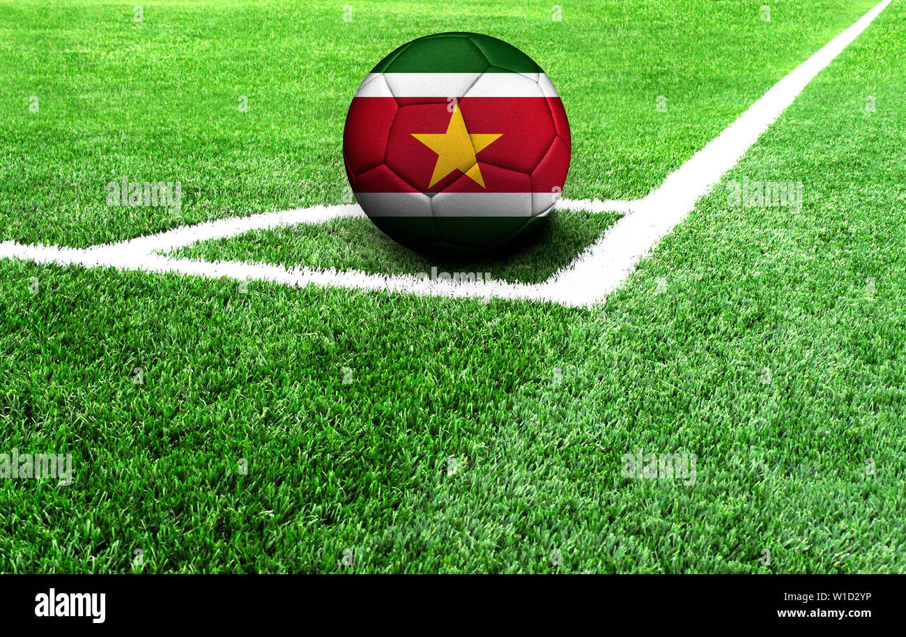 soccer ball on a green field, flag of Suriname - Stock Image
