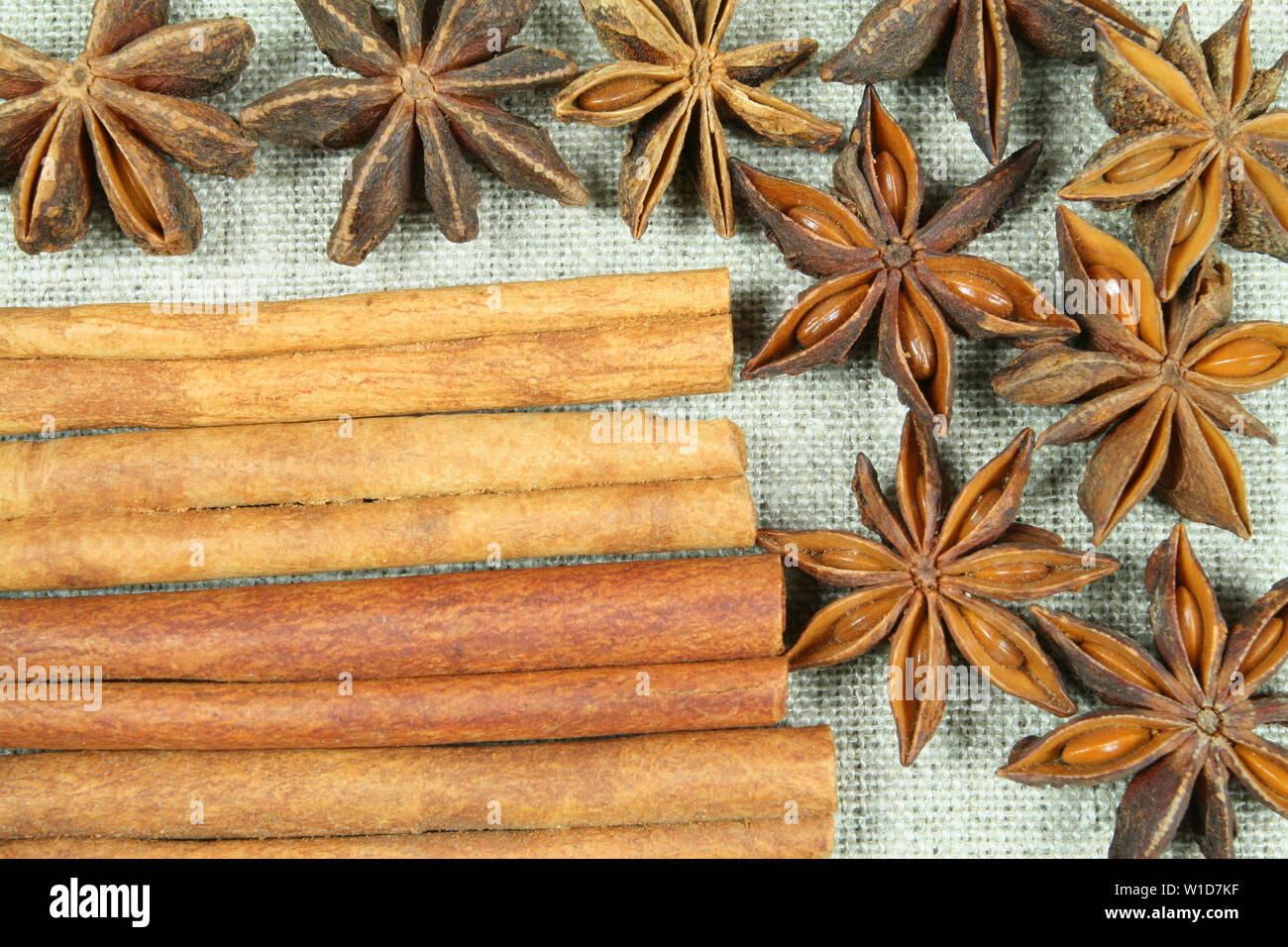 Anise stars and cinnamon sticks on flax background - Stock Image