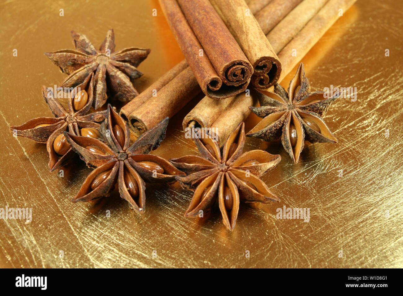 Anise stars and cinnamon sticks on golden cracked plate - Stock Image