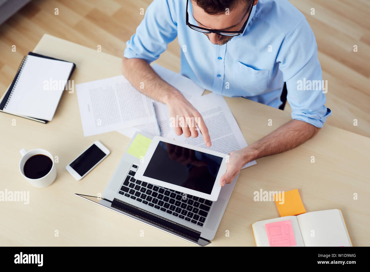 Top view of man using digital tablet sitting at  desk with documents and laptop Stock Photo