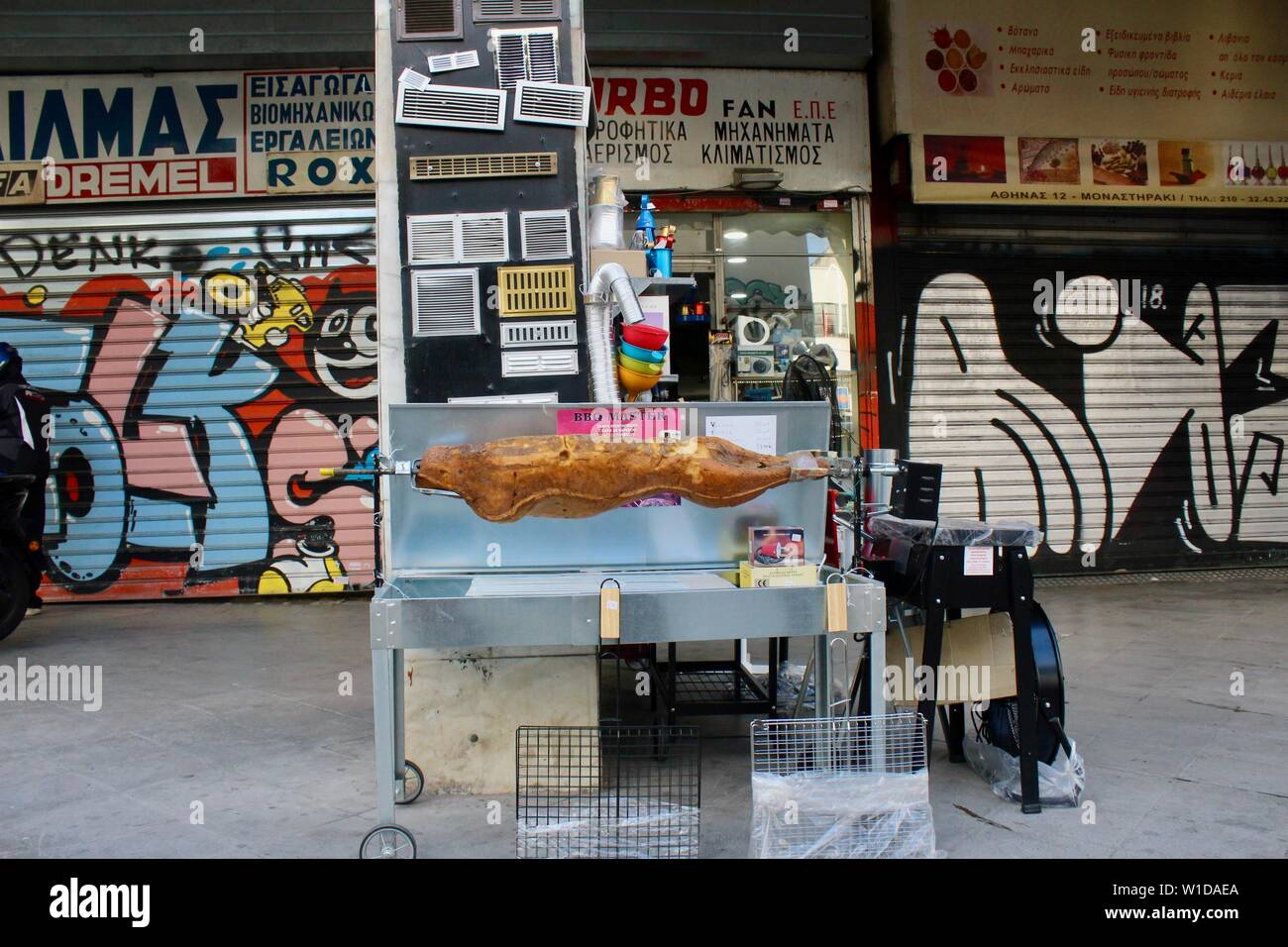 a plastic roast on a spitroast unit outside athens cookware shop greece - Stock Image