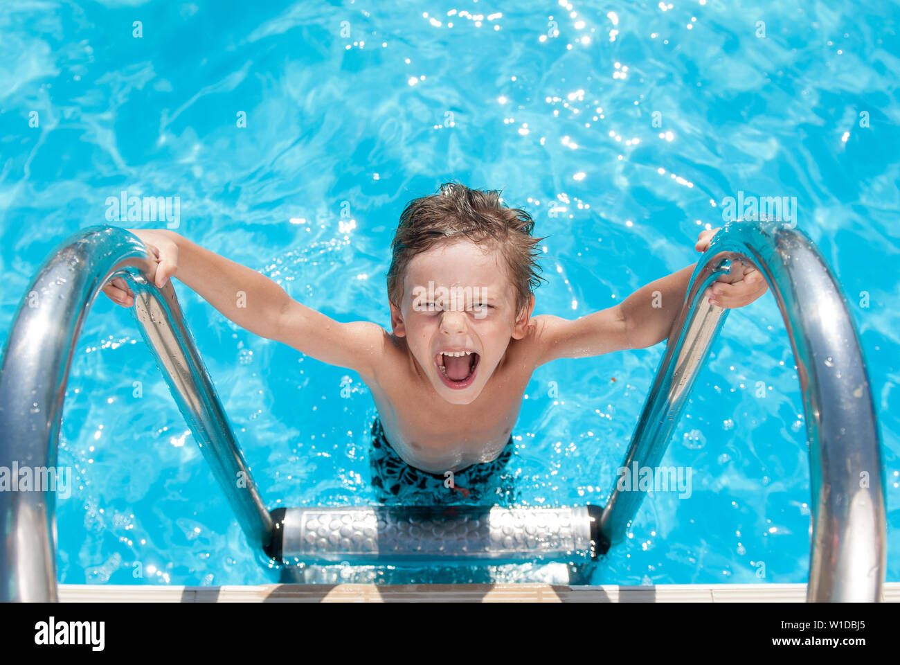 happy beautiful small shouting kid with wet hair standing on chrome handrail in fresh water swimming turquoise outdoors pool in sunny summer holiday d Stock Photo