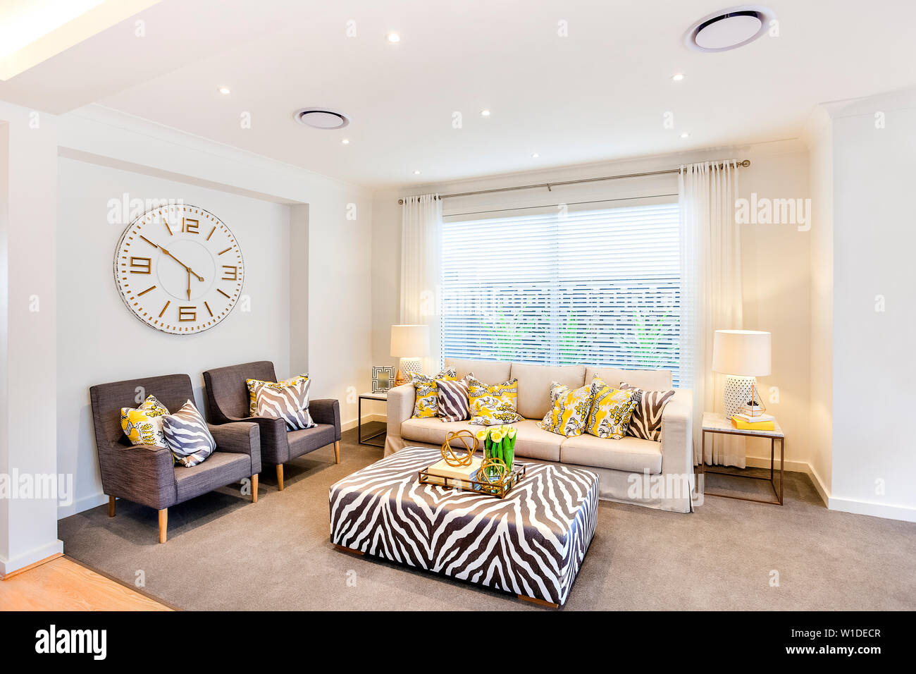 Picture of: Living Room With A Stylish Sofa Set And A Quirky Center Table With Grey Carpeting And Wall Clock Behind The Sofa Chairs Stock Photo Alamy