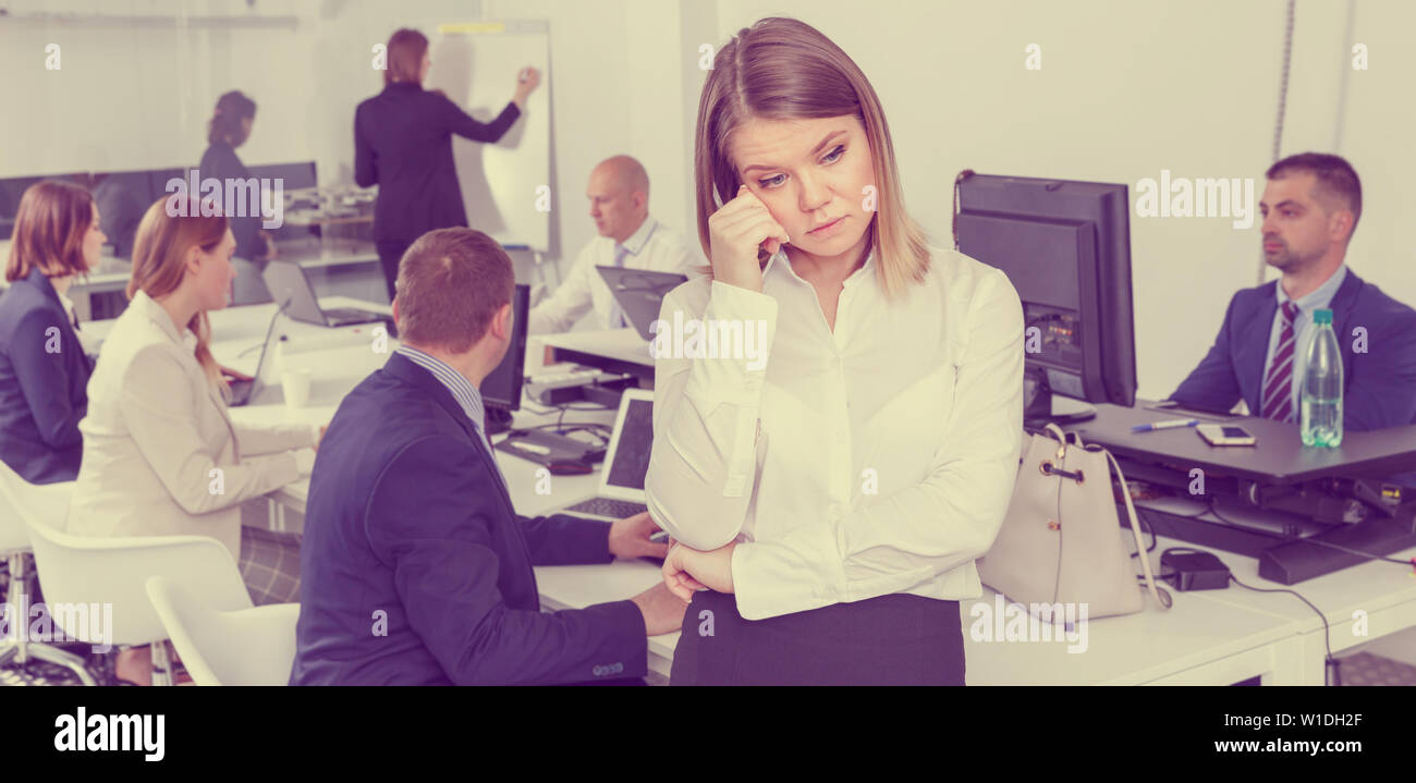 Portrait of unhappy young woman foreground in busy open plan office - Stock Image