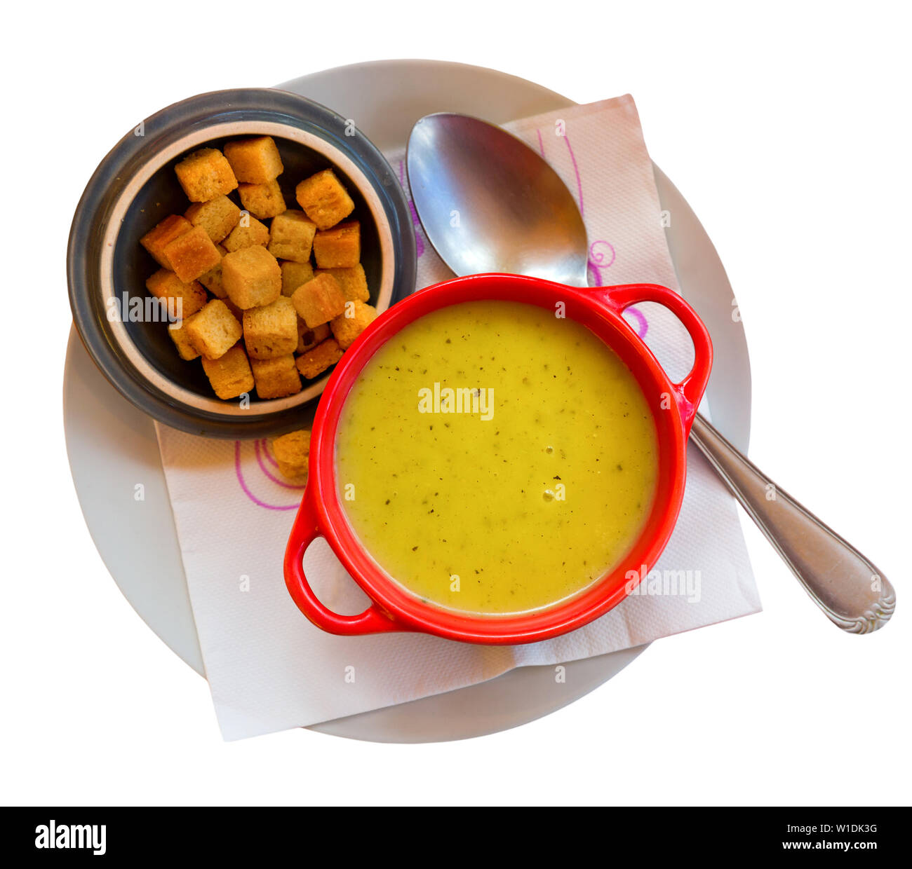 Cream soup of green vegetables garnished with croutons. Isolated over white background - Stock Image