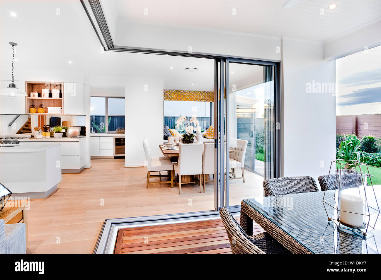 A Stylish Kitchen With A Kitchen Island With A Beautiful Dining Table Next To It With A Glass Sliding Door Partition Leading To The Patio Open Dining Stock Photo Alamy