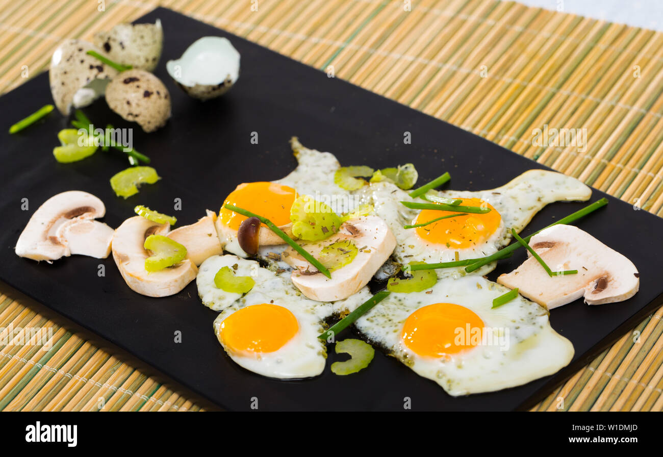 Delicious broken quail eggs with green onion and sliced champignons on black serving board - Stock Image